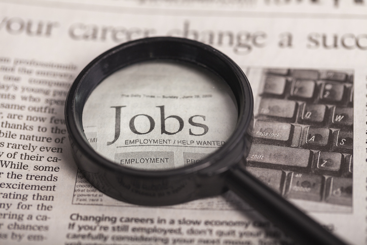 Newspaper with magnifying glass highlighting the word jobs